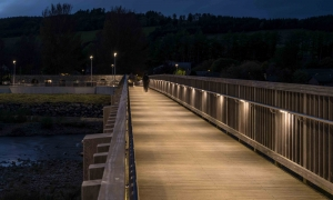 Pedestrian footbridge at night time lit by illuminated handrail